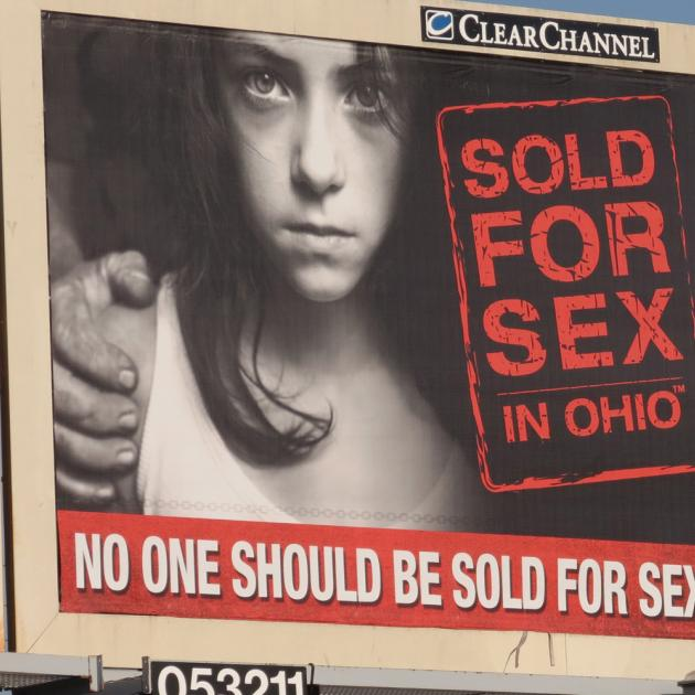 Billboard with a little girl and talking abou human trafficking