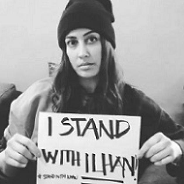 Black and white photo of woman holding small sign saying I Stand with Ilhan