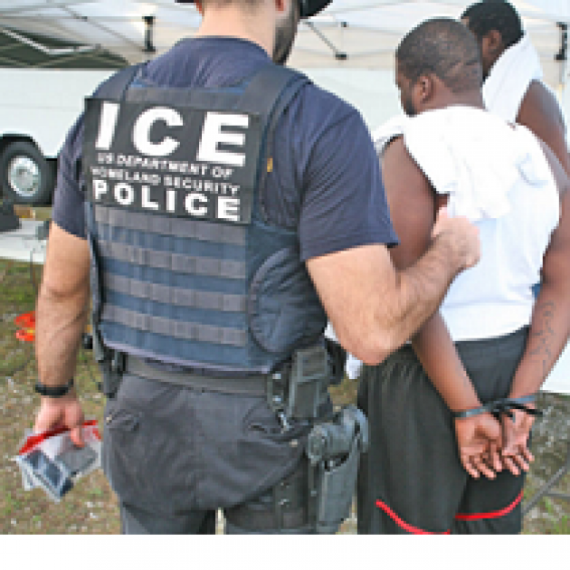 Large white man in uniform that says ICE Police on the back with his back to the camera holding the arm of a dark skinned man in a white t-shirt and shorts with his back to the camera and his hands behind him in handcuffs