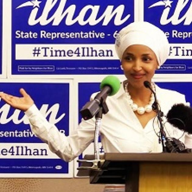 Young woman of color wearing a white hat and suit and pearl necklace standing in front of mics at a podium and signs with her name Ilhan State Representative in the background
