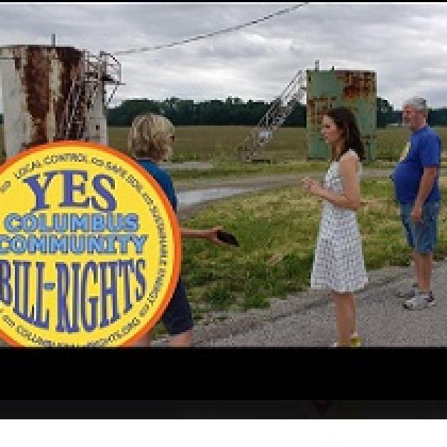 People standing outside in front of weird looking rusty metal structures and the round yellow logo for Columbus Community Bill of Rights