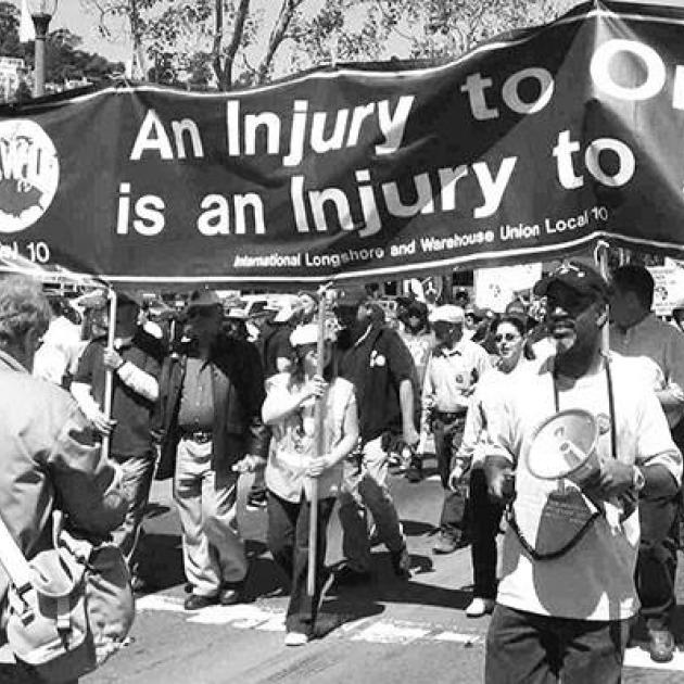 Black and white photo of big banner with words An Injury to one is an injury to all and mostly black people marching with it, some with drums