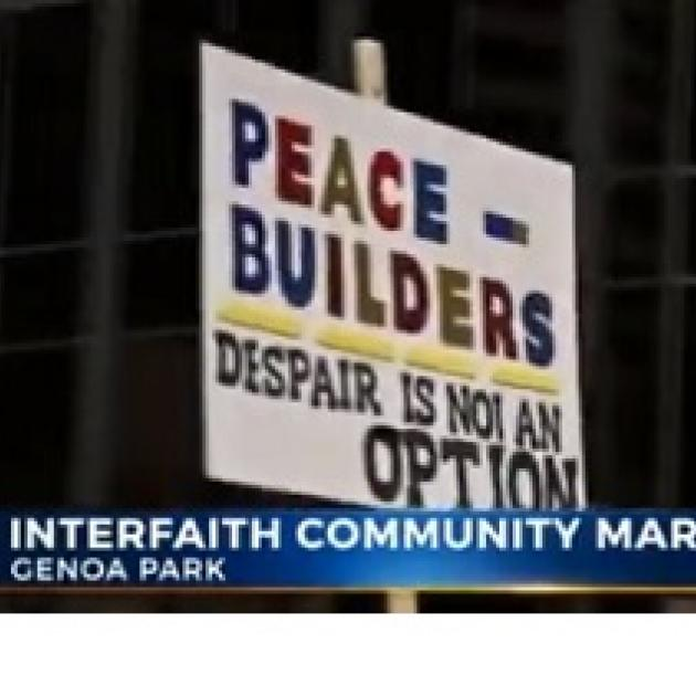 Words on a picket sign Peace Builders Despair is not an option and the banner lower third below saying Interfaith Community March, Genoa Park
