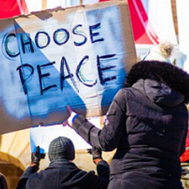 Woman with her back to the camera wearing a large winter coat with furry hood holding a big sign that reads CHOOSE PEACE, she is with a group of people at a rally