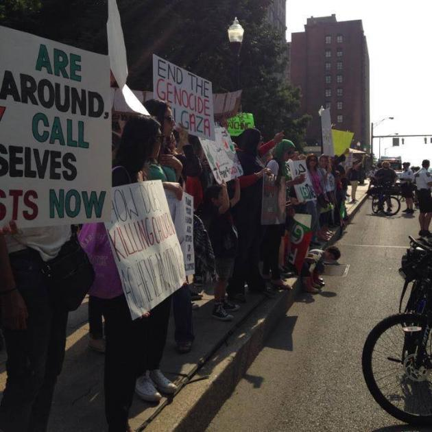 View down a sidewalk with people holding signs demonstrating and some bike cops facing them