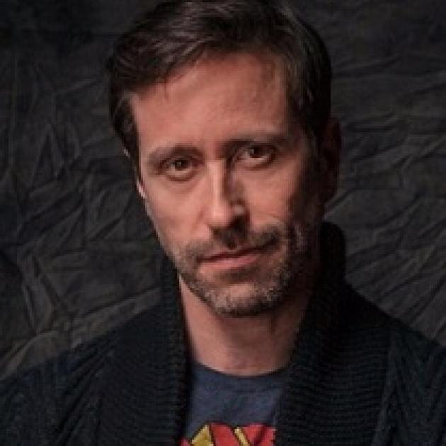 Thin faced man with brown hair and five o clock shadow looking quizzically at the camera
