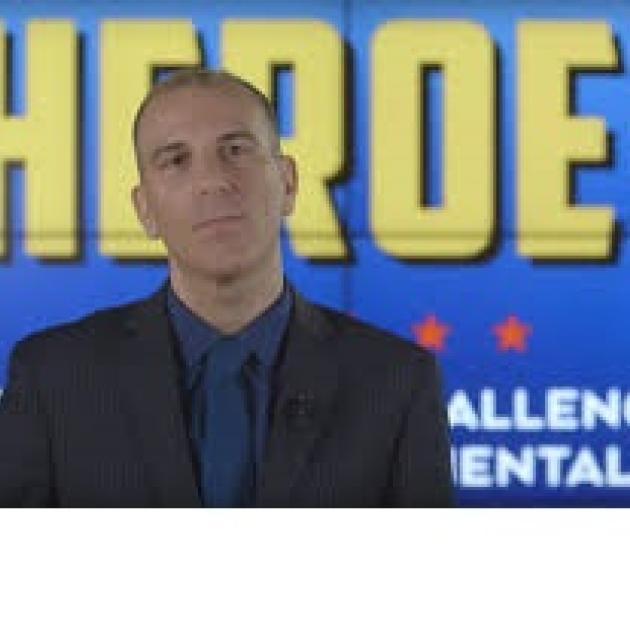 White balding guy against blue background with yellow words saying Heroes