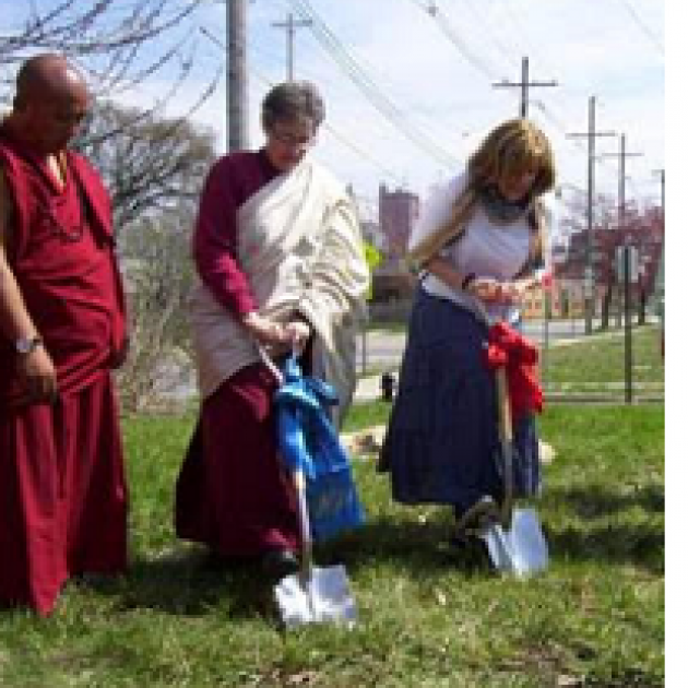 Three people digging into the ground, two wearing Buddhist garb