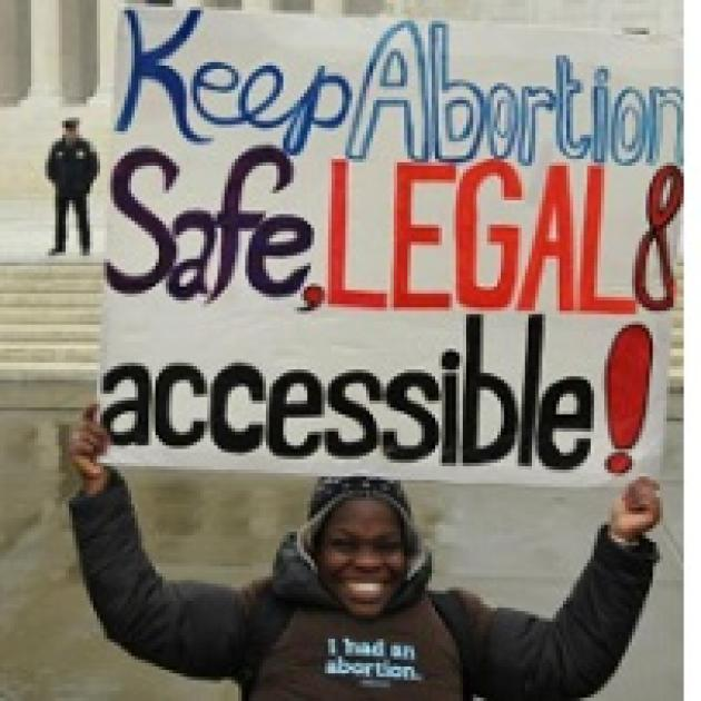 Young black woman smiling with winter clothes on outside an official looking government building holding a sign above her head saying Keep Abortion Safe, Legal & accessible! A cop is standing back in the distance.