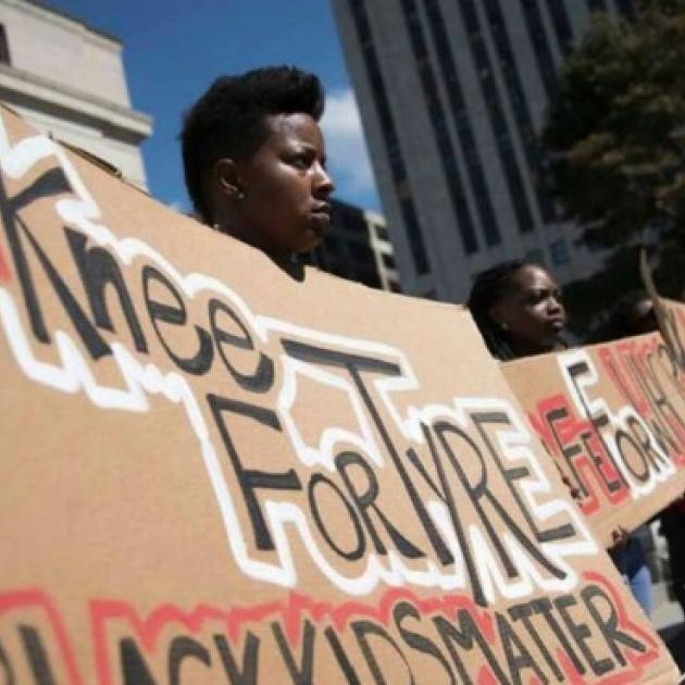 """Black people holding a banner that says """"Knee for Tyye, Black Kids Matter"""""""