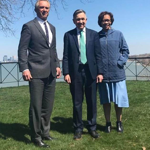 Three people standing outside on the grass with  body of water behind them, a tall white man in a suit with gray hair, and shorter white man in a suit and a black woman with glasses