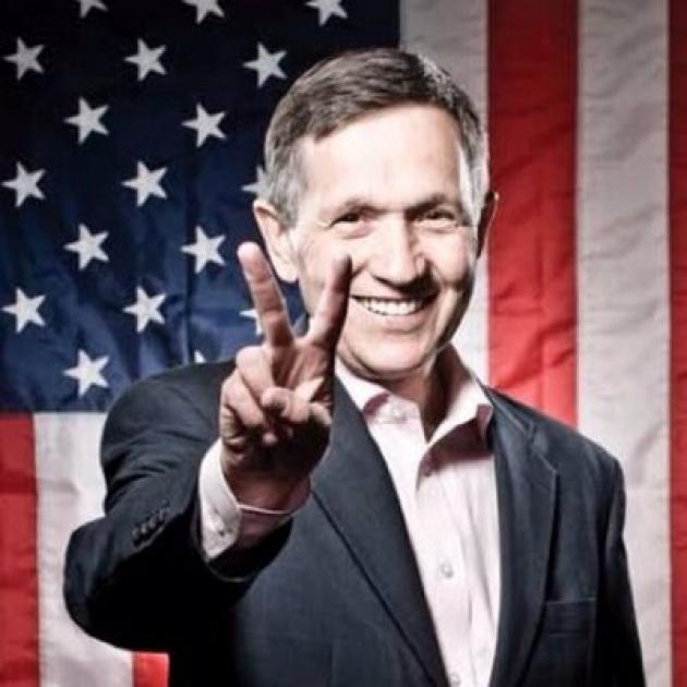 White middle aged man smiling an making a peace sign in front of a flag