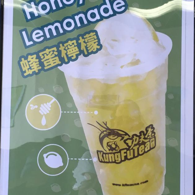 A sign with a cup with yellow liquid and words Kung Fu Tea