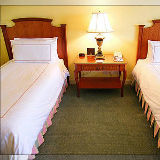 Two single beds separated in a bedroom