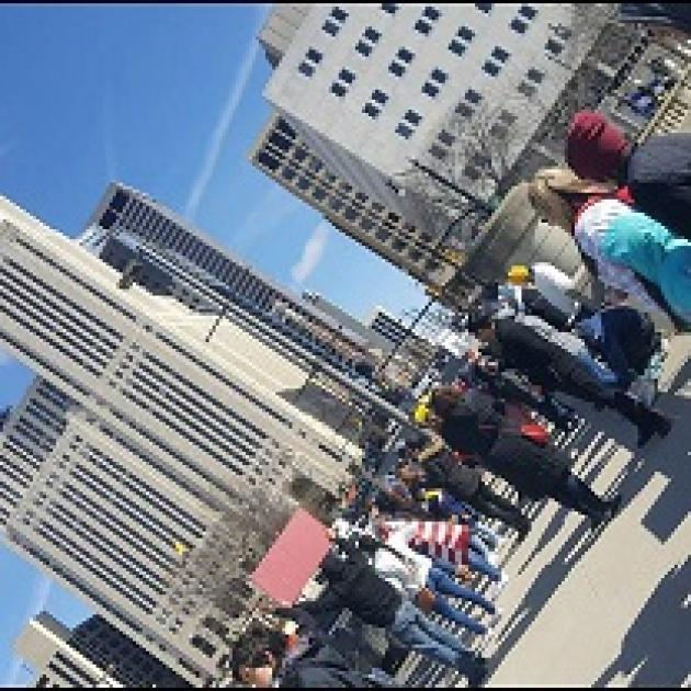 Sideways photo of downtown skyscraper with people standing below protesting