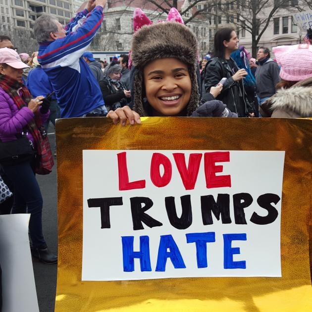 Young woman holding Love Trumps Hate sign