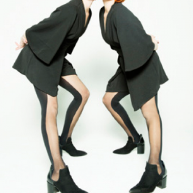Two women with red hair and black outfits leaning towards each other