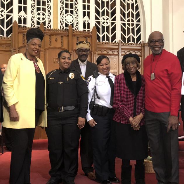Several black men and women posing at a church