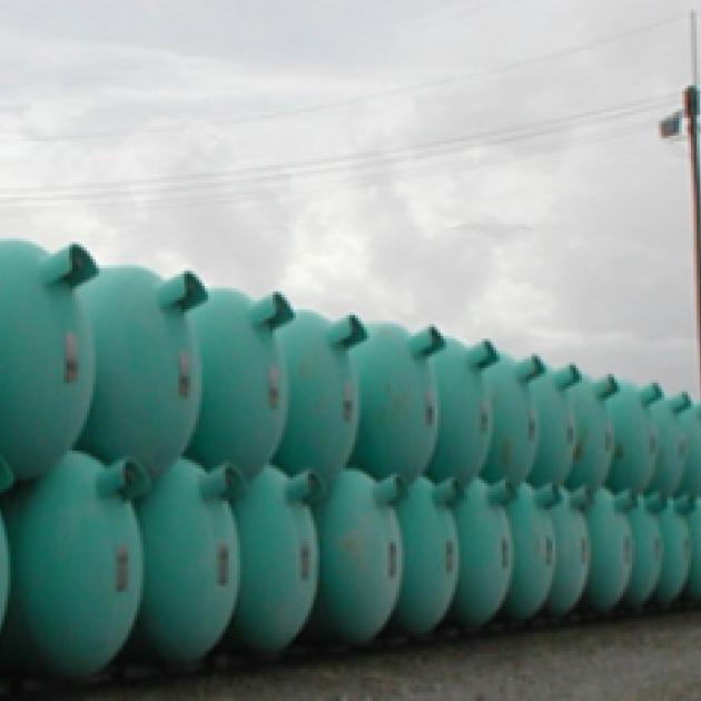 Dozens of blue green barrels lined up