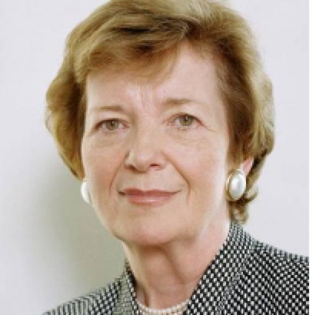 Middle aged white woman with earrings and a black and white suit