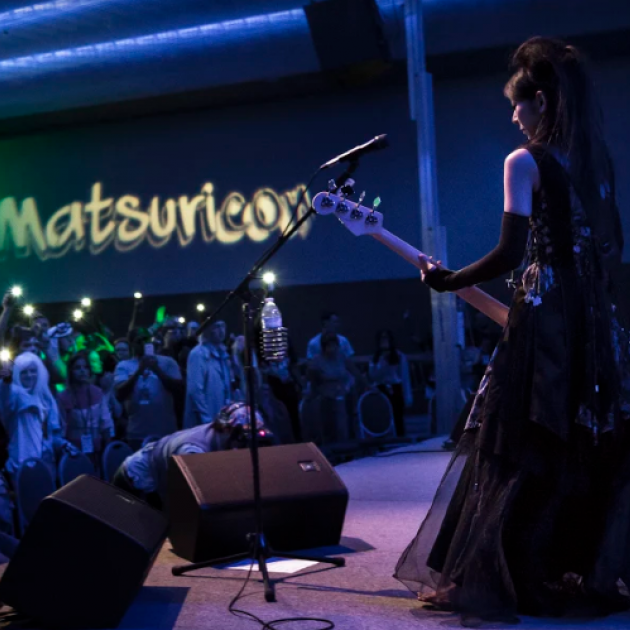 White woman in a Renaissance looking gown playing guitar on stage to a crowd standing under the sign Matsuricon