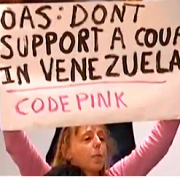 Blonde woman in pink shirt holding big sign above her head that says OAS: Don'ts support a coup in Venezuela