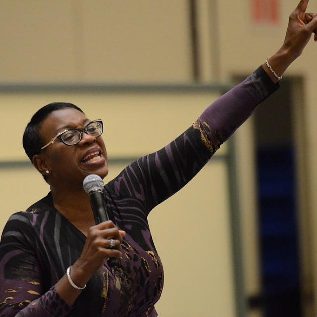 Black woman giving a speech raising her arm in the air