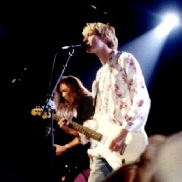 Kurt Cobain singing into a mic and a guitarist behind him