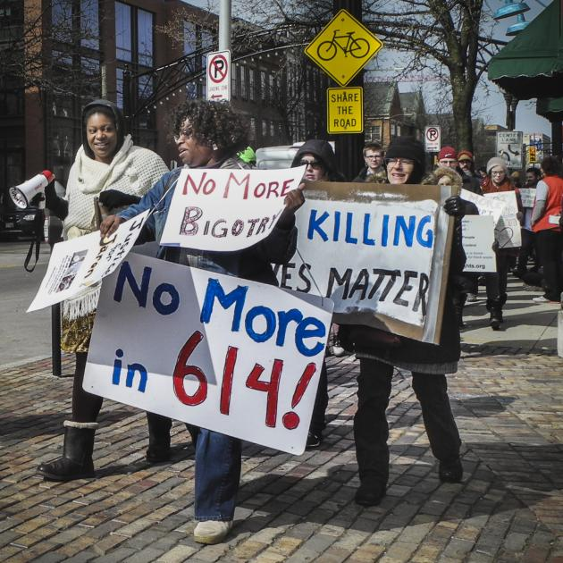 People marching down High Street holding signs that say No More in 614, no more bigotry, black lives matter.