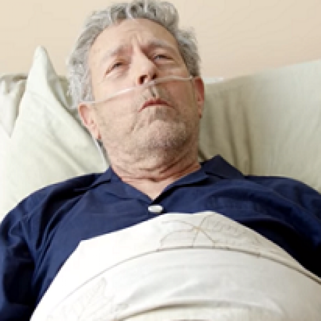 Old man with oxygen in his nose, in a bed