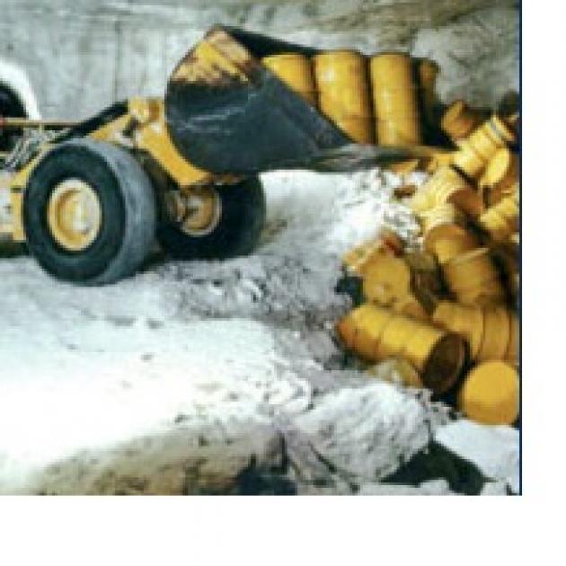 Bulldozer pushing yellow barrels into a ditch
