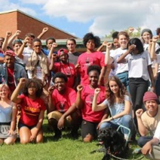 Young people posing outside wearing mostly red shirts with their fists in the air