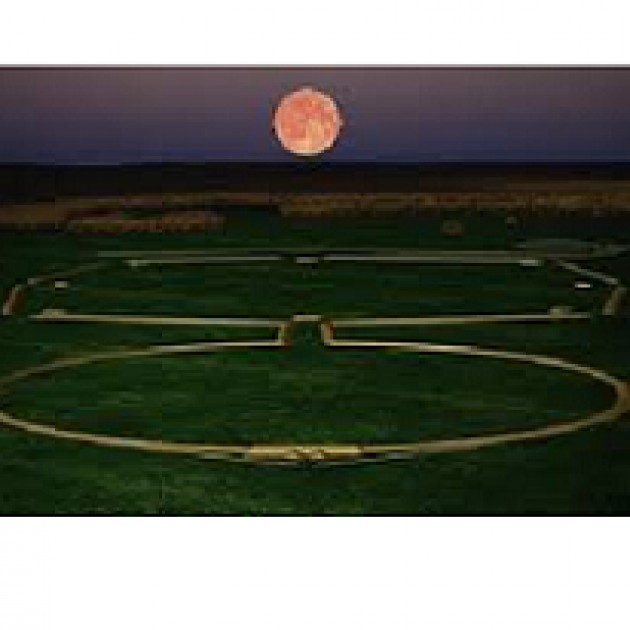 Green ground and dusky sky with huge red moon and a design on the ground