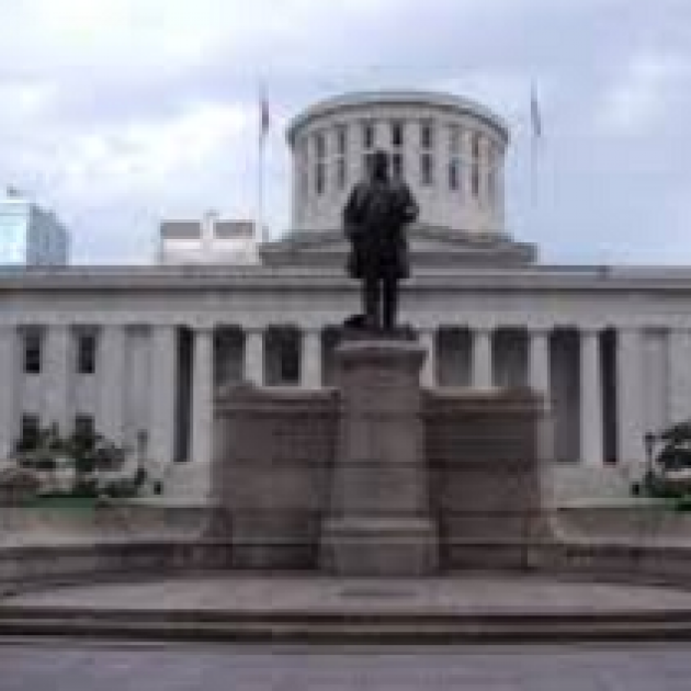Large black statue of a man on a pedestal in front of a large white government building with many columns