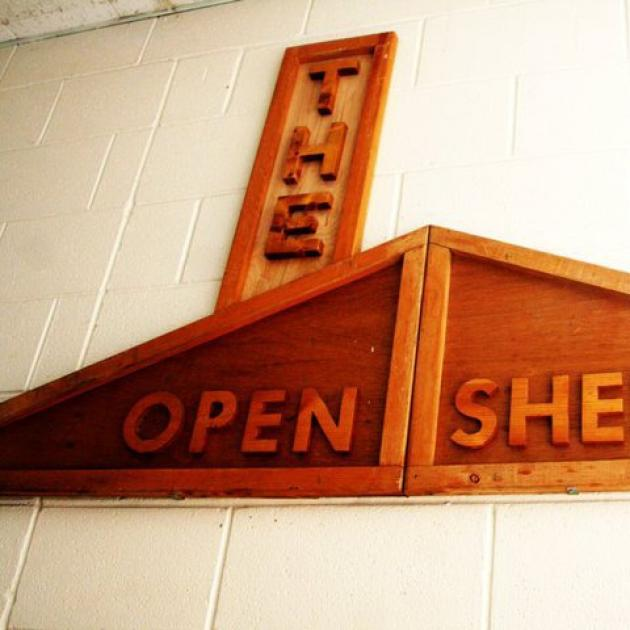 Wooden sign saying The Open Shelter