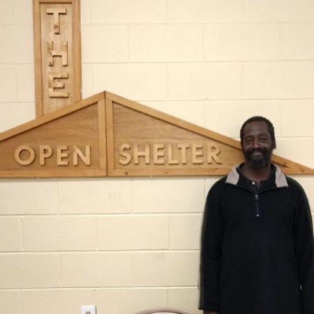 Open Shelter sign and man standing next to it