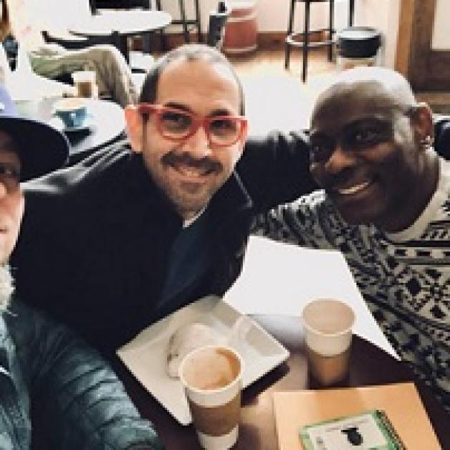A balding white guy with red framed glasses and facial hair smiling sitting at a table with his arm around a bald black man in a white and black designed sweater also smiling