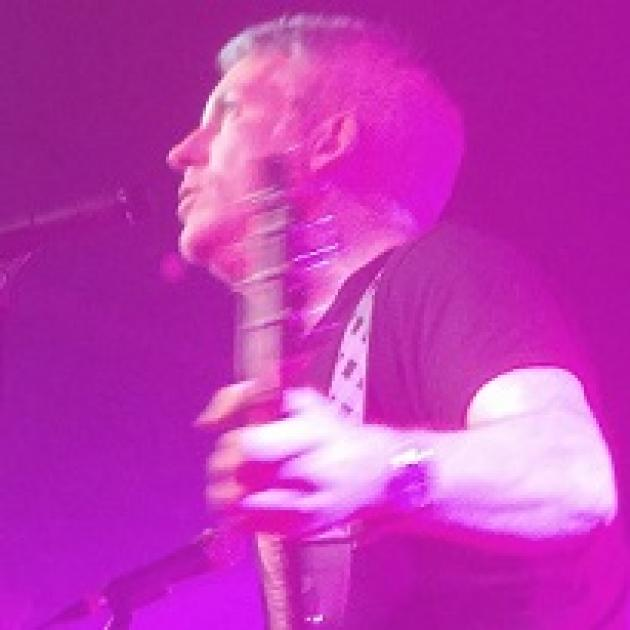 Purple lighted picture of white man performing side view holding a guitar