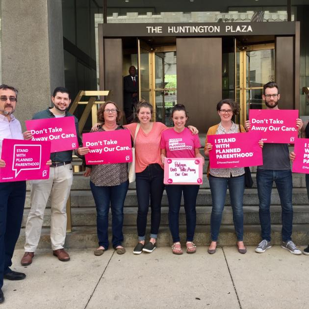 People with pink signs standing outside a government building