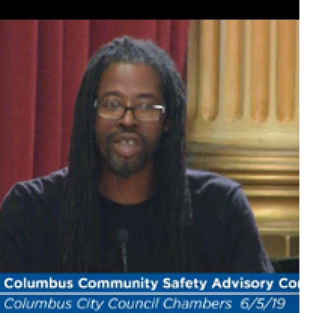 Black man in dreads talking at a mic