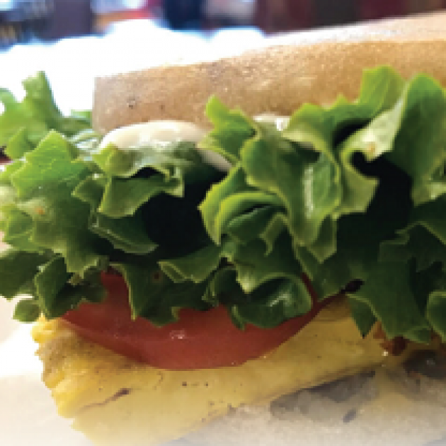 Close up of a sandwich with lettuce and tomato spilling out the side