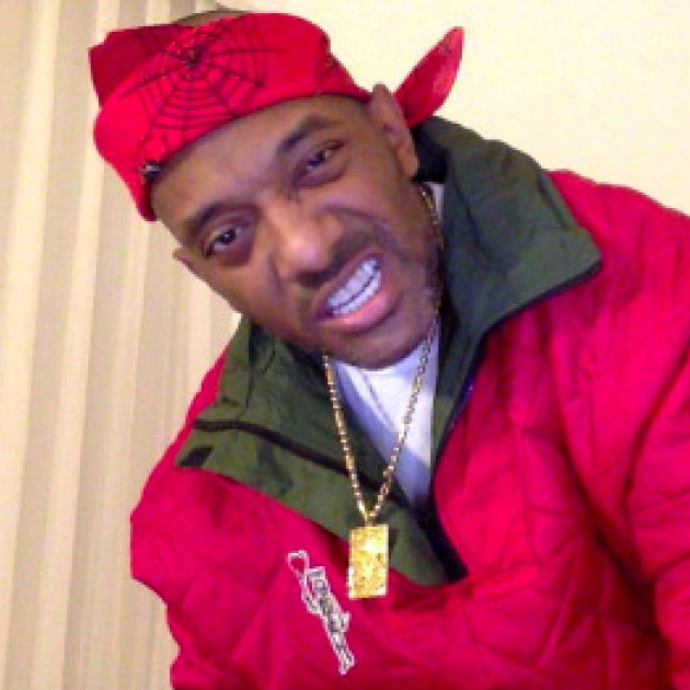 Black man in red jacket with red doo rag scarf on head with gold necklace, making a sneering face