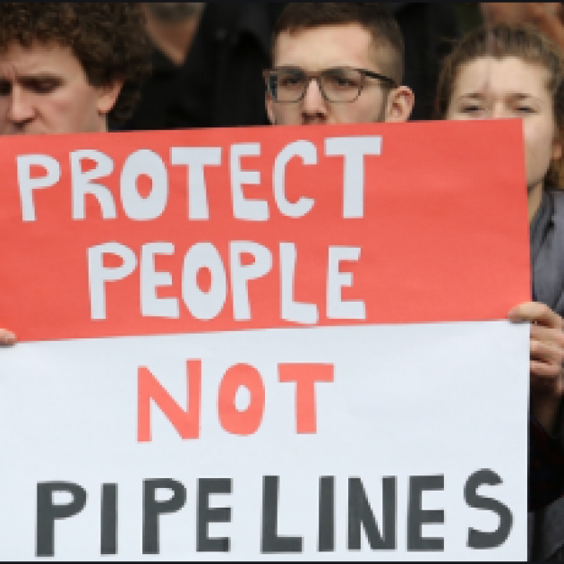 Demonstrators holding a sign that reads Protect People not Pipelines