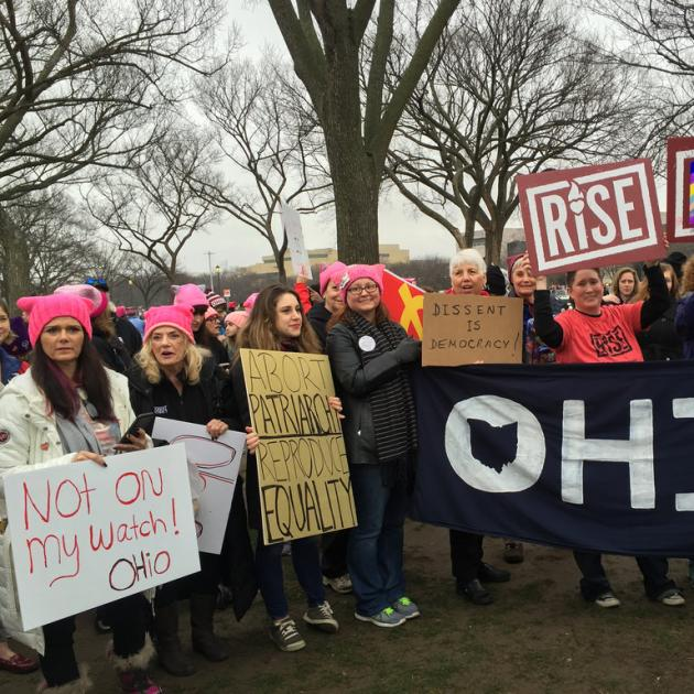 Women outside wearing pink winter hats holding signs and a big banner that says OHIO