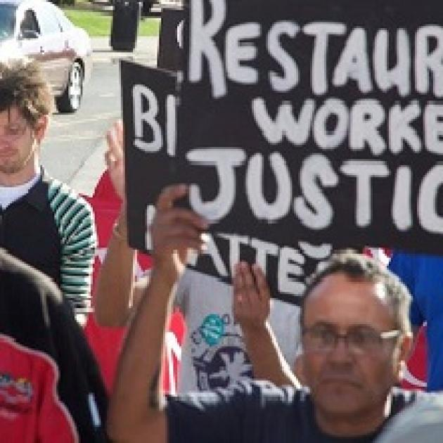 People protesting with sign Restaurant worker justice