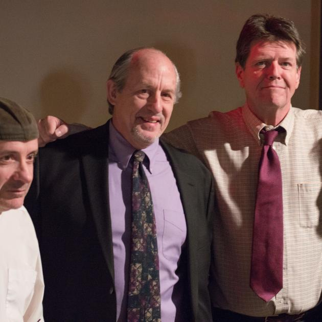 Four middle aged white guys, some in suits, standing together with their arms around each other