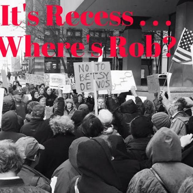 Black and white photo of people at a rally downtown with words It's Recess...Where's Rob?