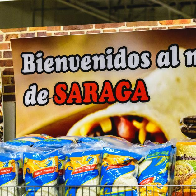Sign in back of food at a grocery store saying Bienvenidos al de Saraga