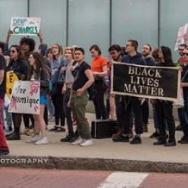 Several young people on a sidewalk at a rally holding a banner saying Black Lives Matter