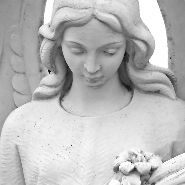 White statue of an angel, a woman with long flowing hair looking down and holding flowers in her arms